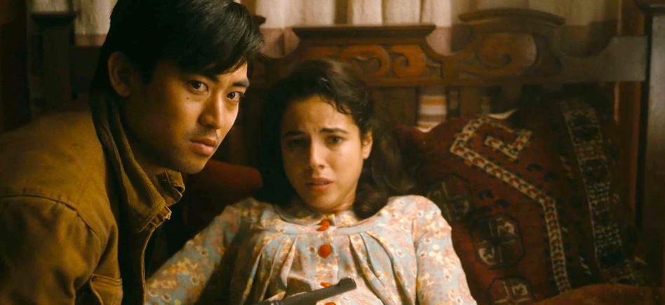 Chester and Luz sit on a bed looking concerned
