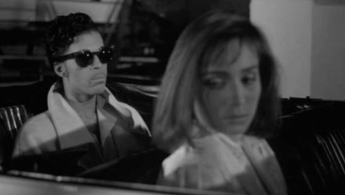 Christopher Tracy (Prince) and Mary Sharon (Kristin Scott Thomas) sit in silence in a car in Under the Cherry Moon.