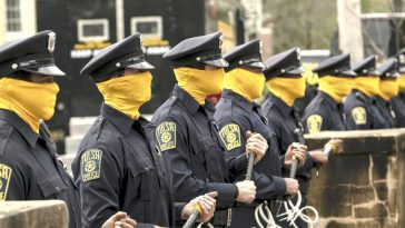 A group of law enforcement officers stand in a line, masks covering their faces