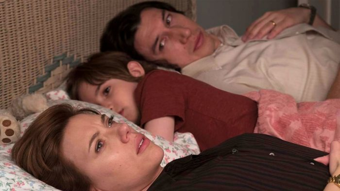 Nicole looks at the wall laying in bed next to her son and Charlie who is staring at her