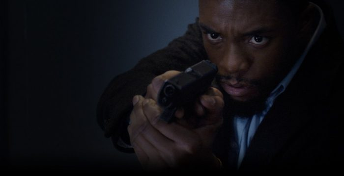 Chadwick Boseman points his gun at an unseen criminal