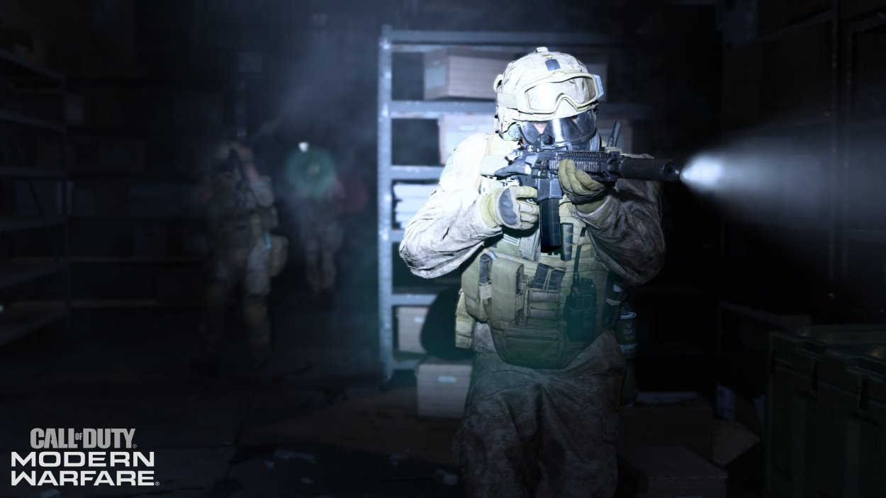 A soldier moves around a building in the dark with a bright light shining from his gun
