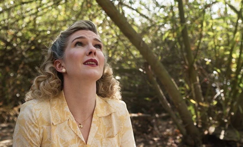 Lavinia looks up to the sky as she follows the sound of her sons voice in the woods