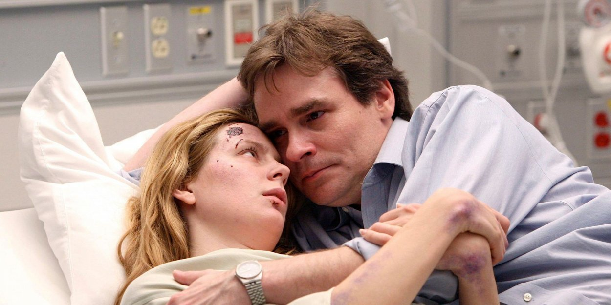 An emotional Wilson holds Amber, who is cut up and bruised, in a hospital bed