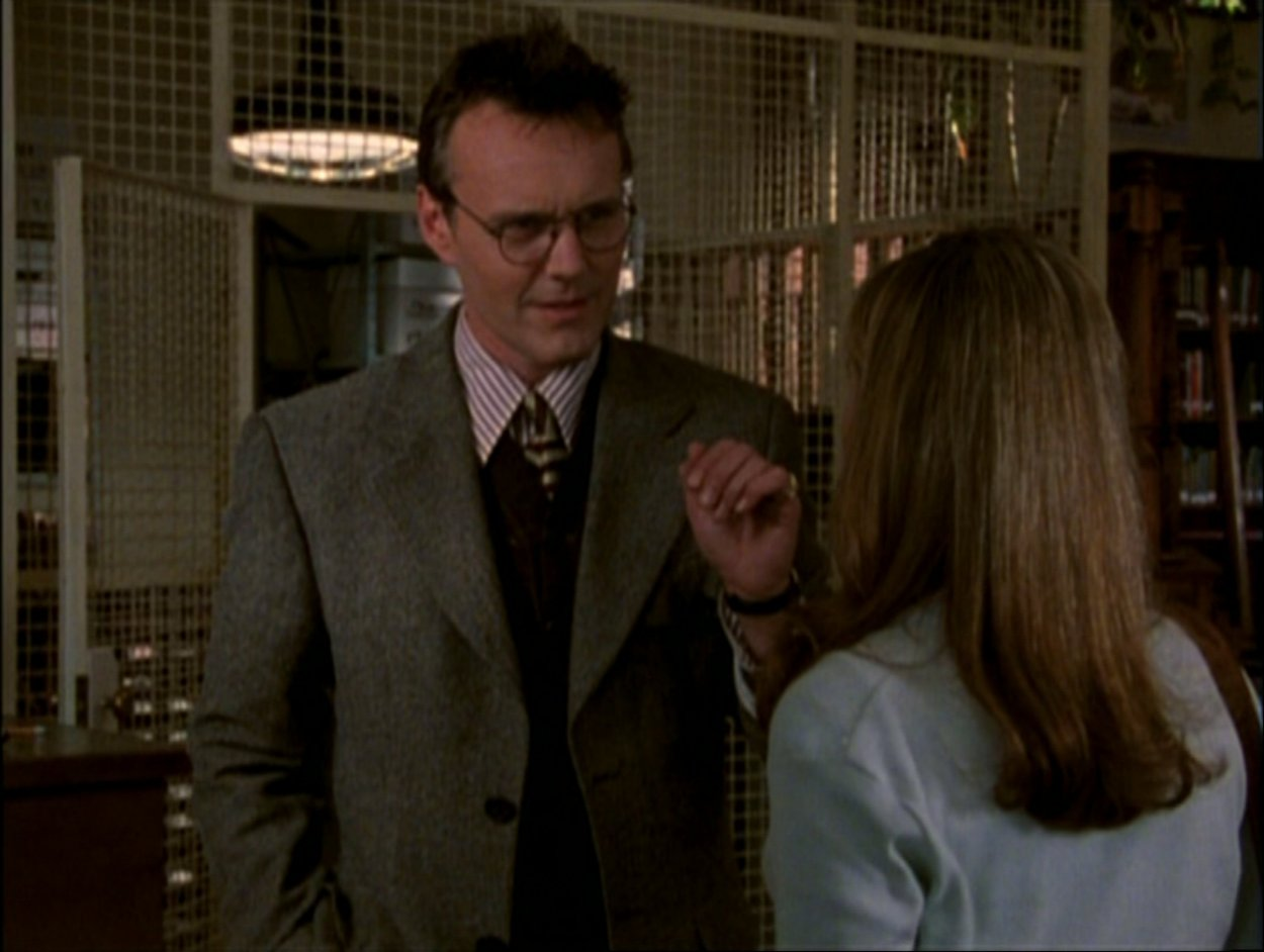 Giles talks to Buffy in the library
