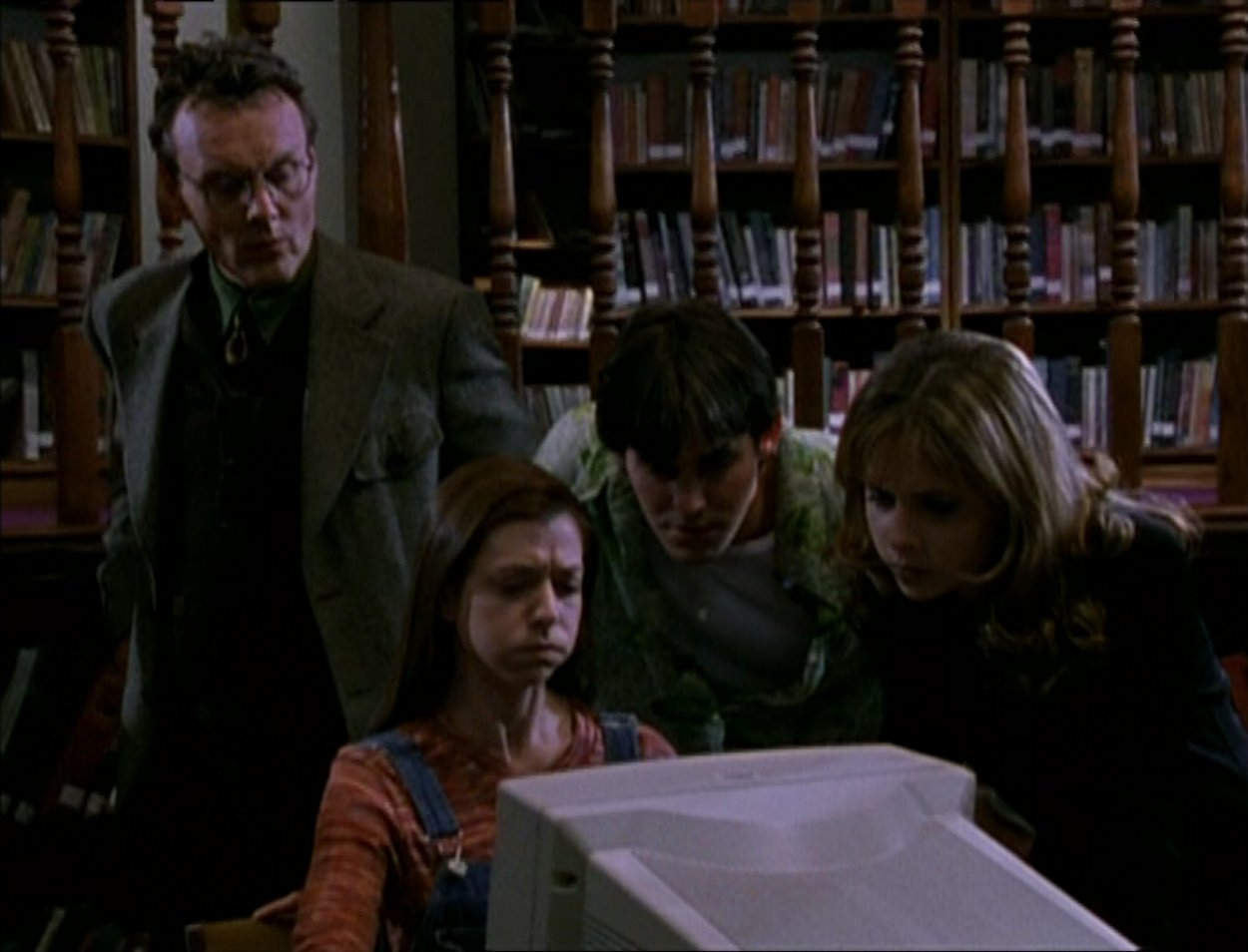 Giles, Willow, Xander and Buffy research in the library