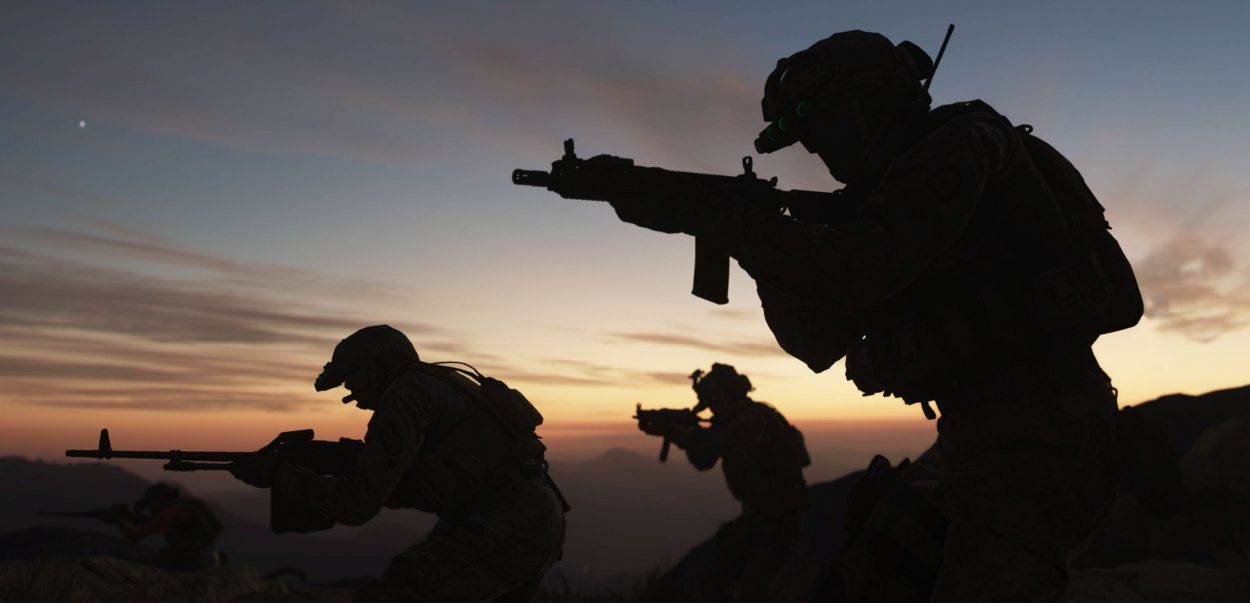 3 silhouettes of soldiers with guns drawn at sunrise
