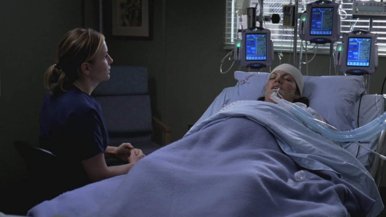 Callie lies in a hospital bed with her head bandaged and a tube in her mouth. Arizona sits at her bedside.