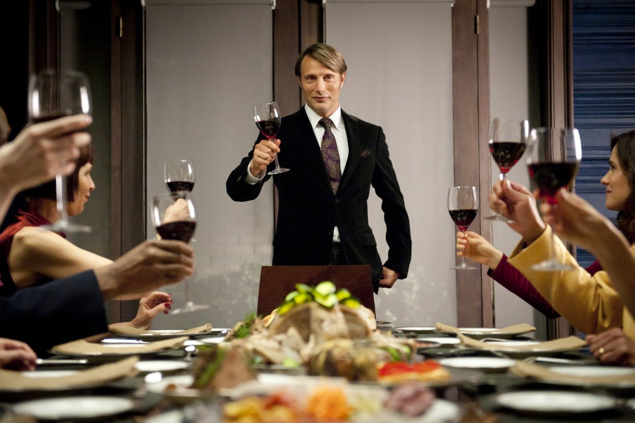 Lecter makes a toast from the head of his table. About 8 guests hold up glasses of red wine