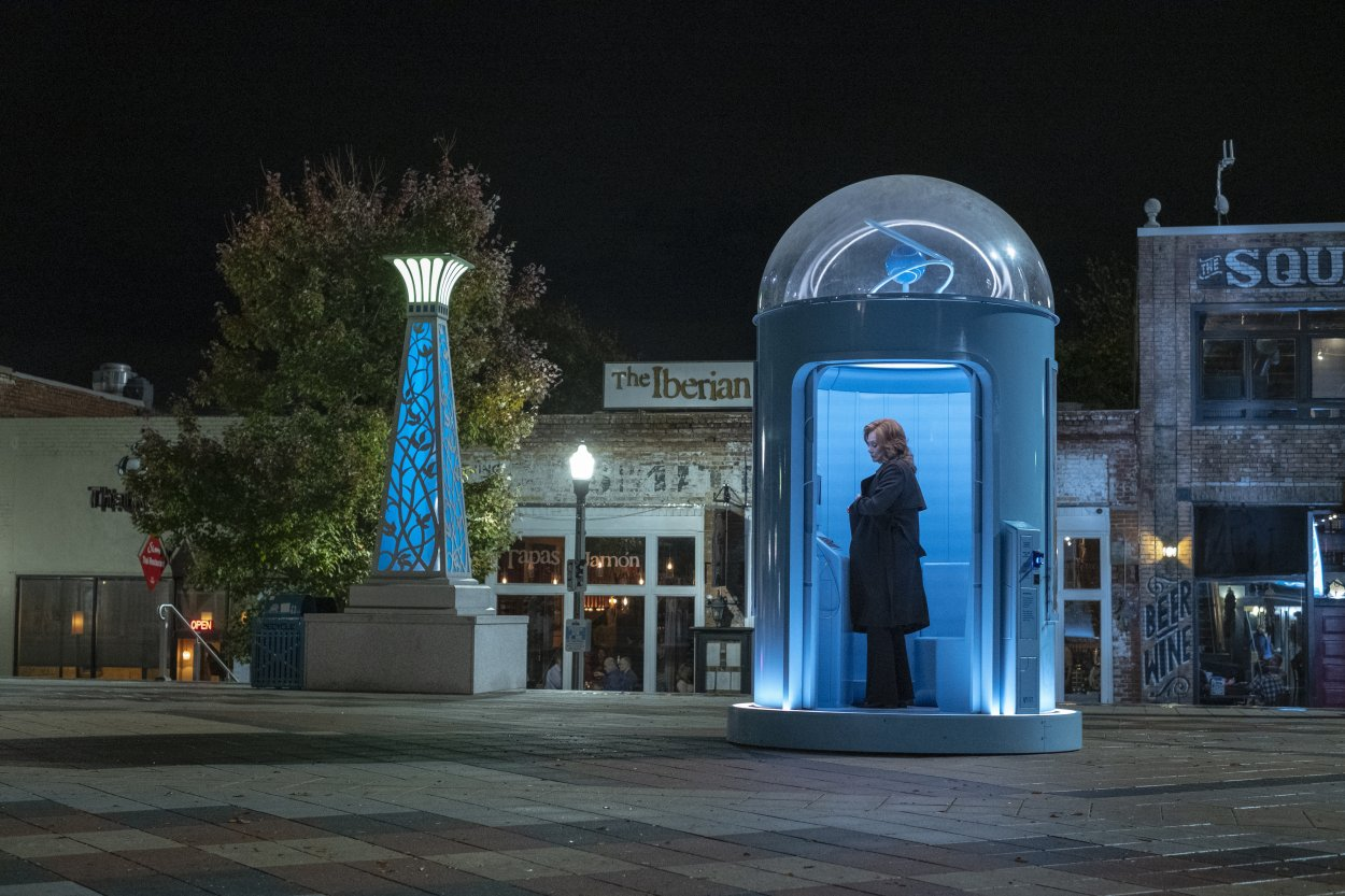 Laurie Blake in a blue booth sending a message to Dr. Manhattan