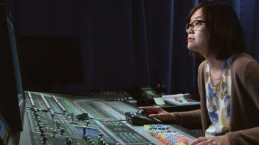 Ai-Ling Lee uses a soundboard to edit sound effects into a film