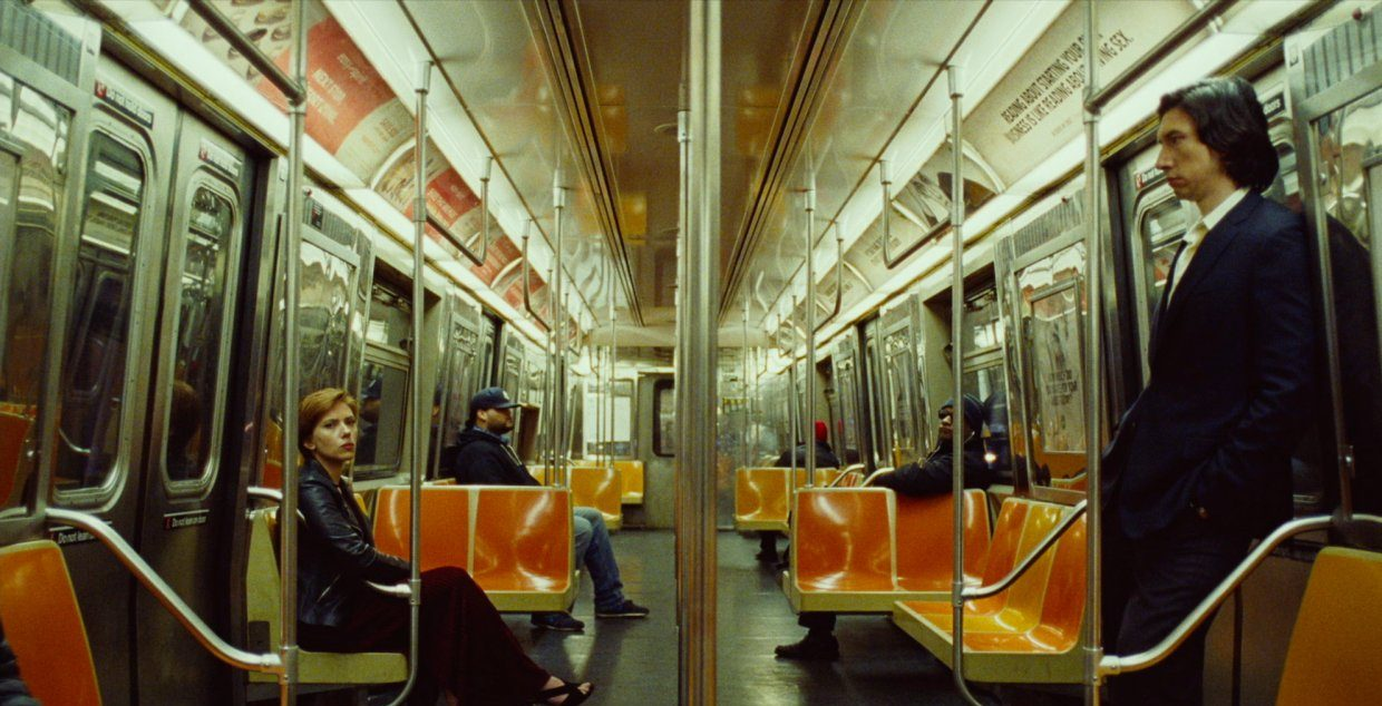 Nicole sits on a quiet subway car with Charlie standing across from her