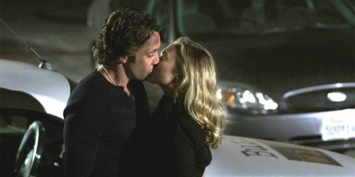 Mick and Beth kissing in a parking lot