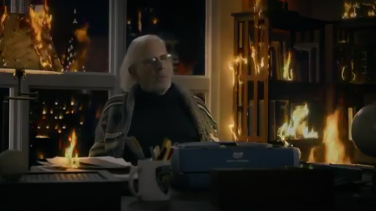 John Rothstein sits at a typewriter, curtains on fire behind him