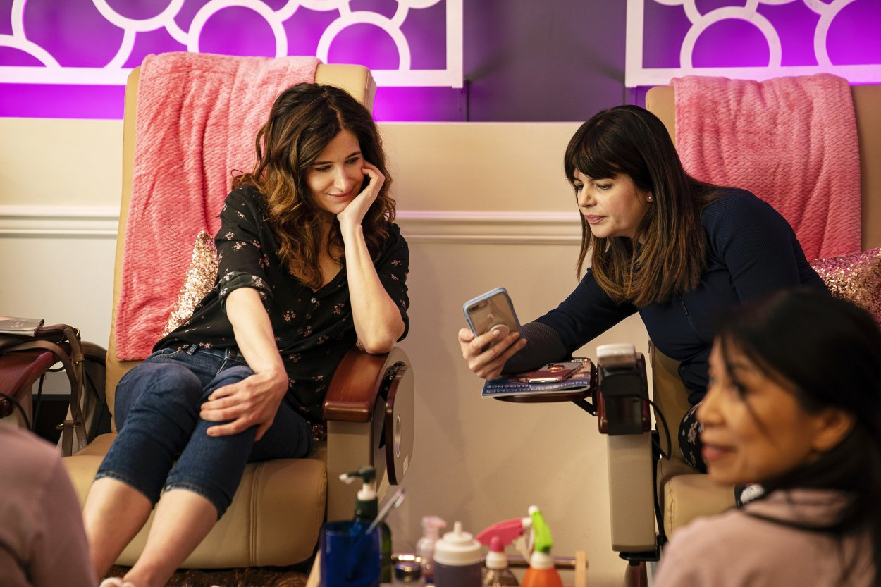 Jane shows Eve pictures on her phone as they sit in neighboring pedicure chairs