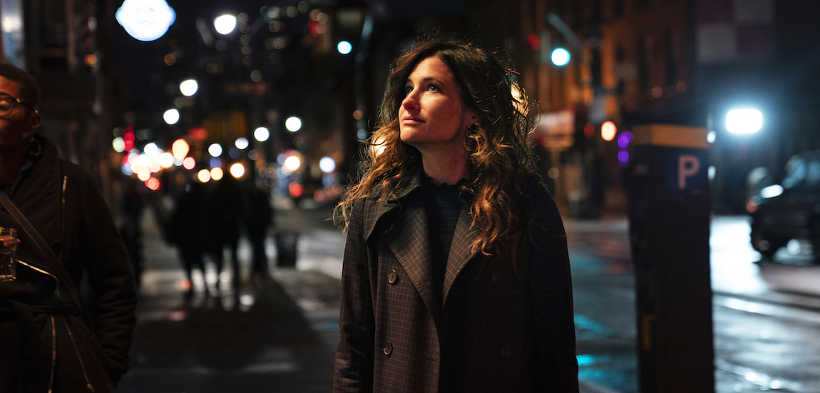 Eve stands on a NYC sidewalk at night looking satisfied