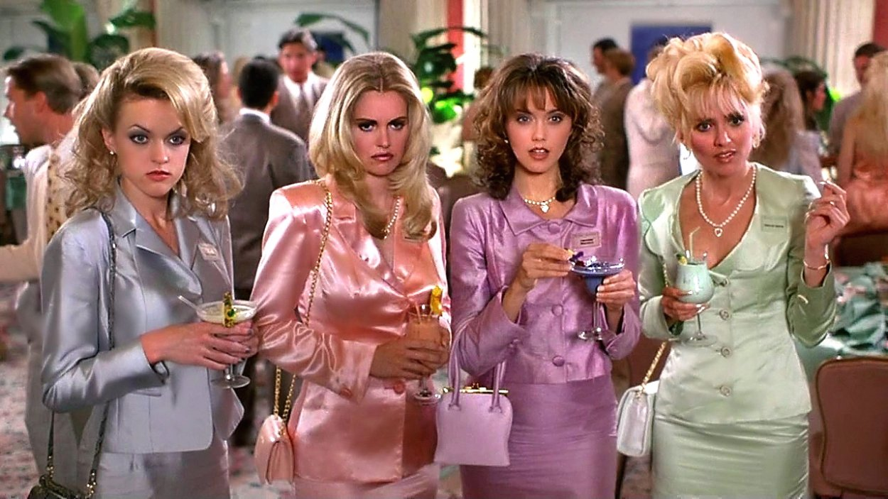 Christie Masters and her clique stare in bewilderment at Romy white at their high school reunion