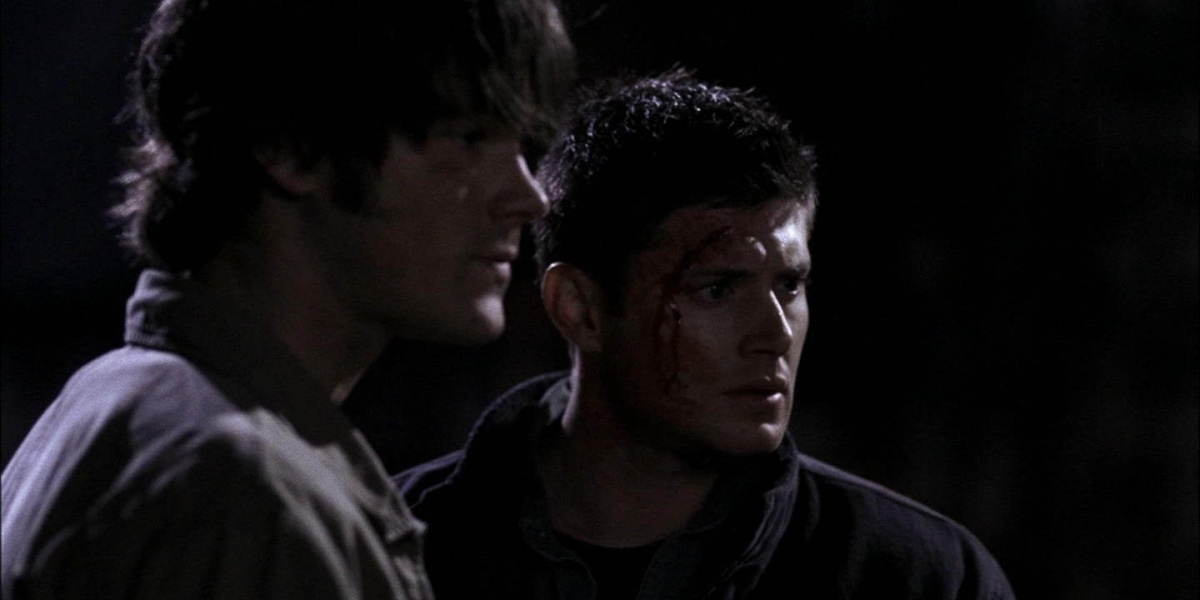 Sam and Dean looking at something in front of them somberly while standing in the dark, with blood from a cut on the left side of Dean's head