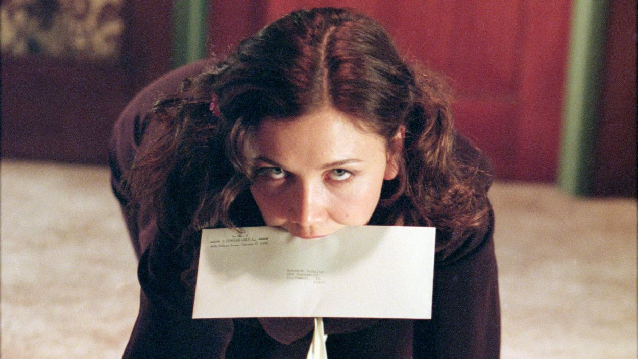 Lee Holloway on her hands and knees with an envelope in her mouth in Secretary