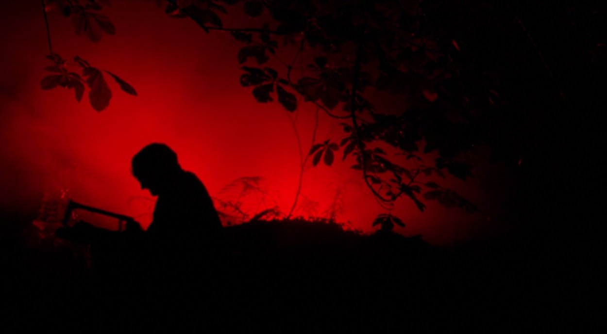 Graveside silhouette of a figure against a red background