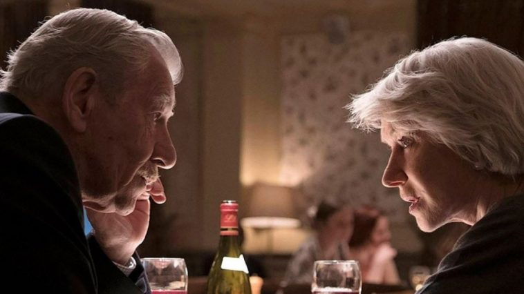 Ian McKellen and Helen Mirren speak with each other closely at a dinner table in The Good Liar