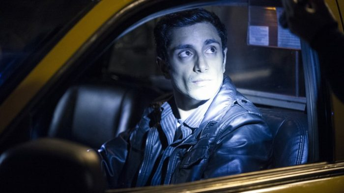 Naz sits in the driver's seat of his father's cab, has a light shining in his face