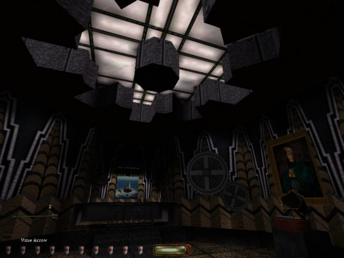Garret stands in an industrialized room with gears on the walls and a few portraits of individuals. In the ceiling there is a giant skylight.