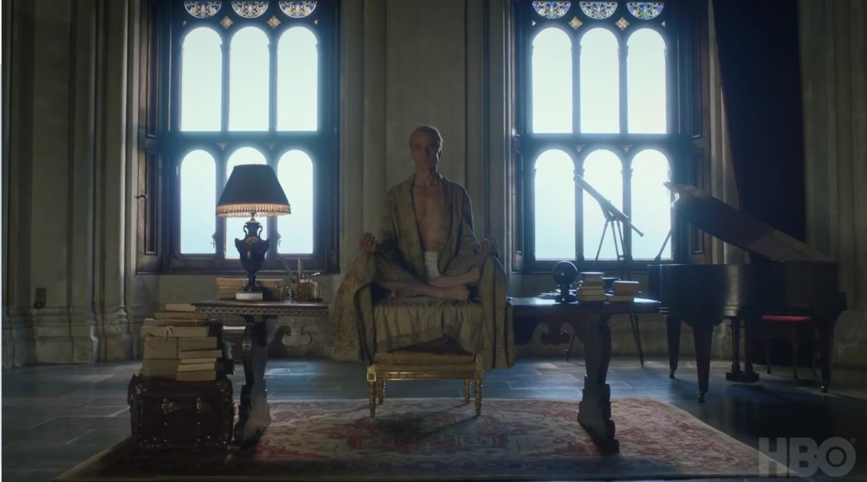 Watchmen - The Lord of a Country Manor sits in a robe, cross-legged, on a ornate wood desk