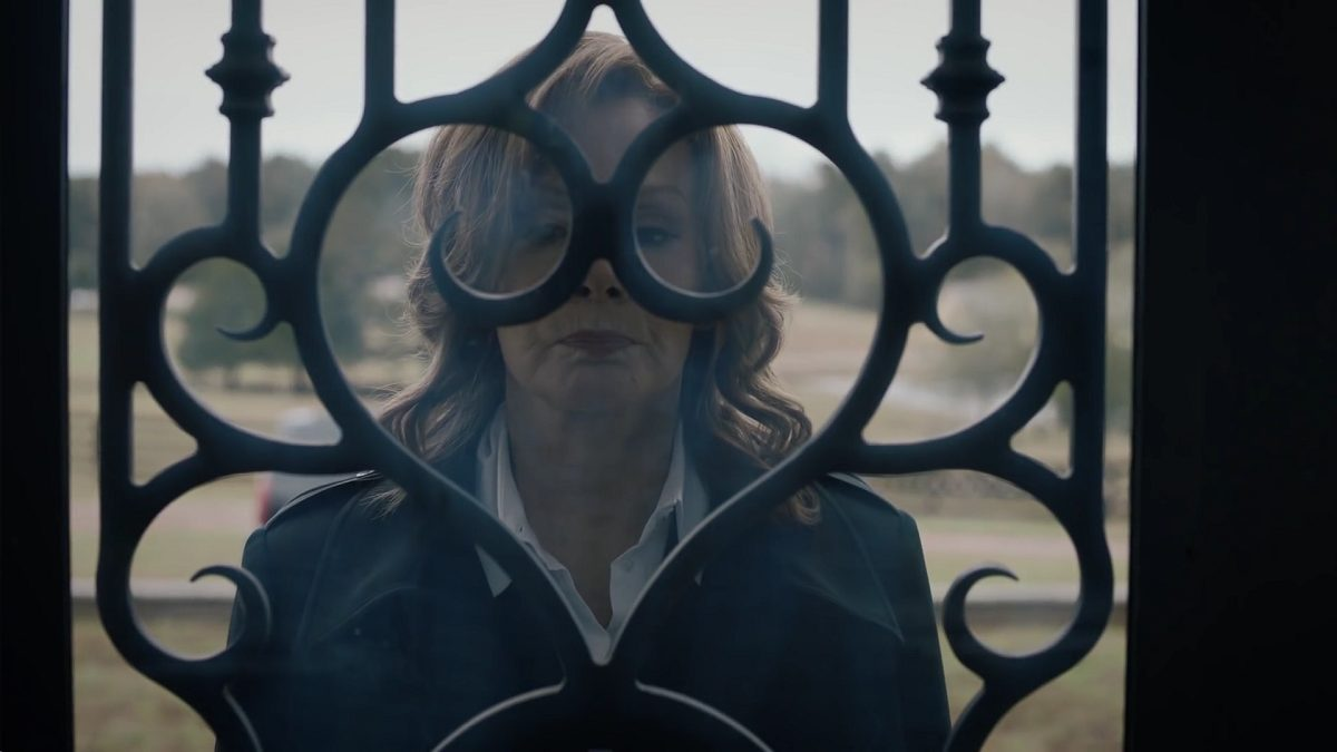 Watchmen - Laurie stands outside a glass door, the intricate iron work frames her face like a mask