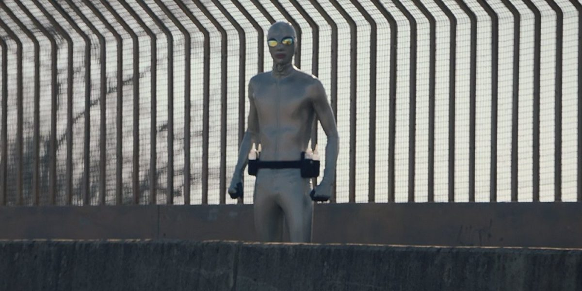 Watchmen - Lubeman stands on a highway overpass looking in our direction