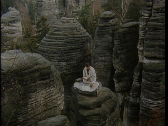 Faust stands on a rock tower as he tries to summon the devil