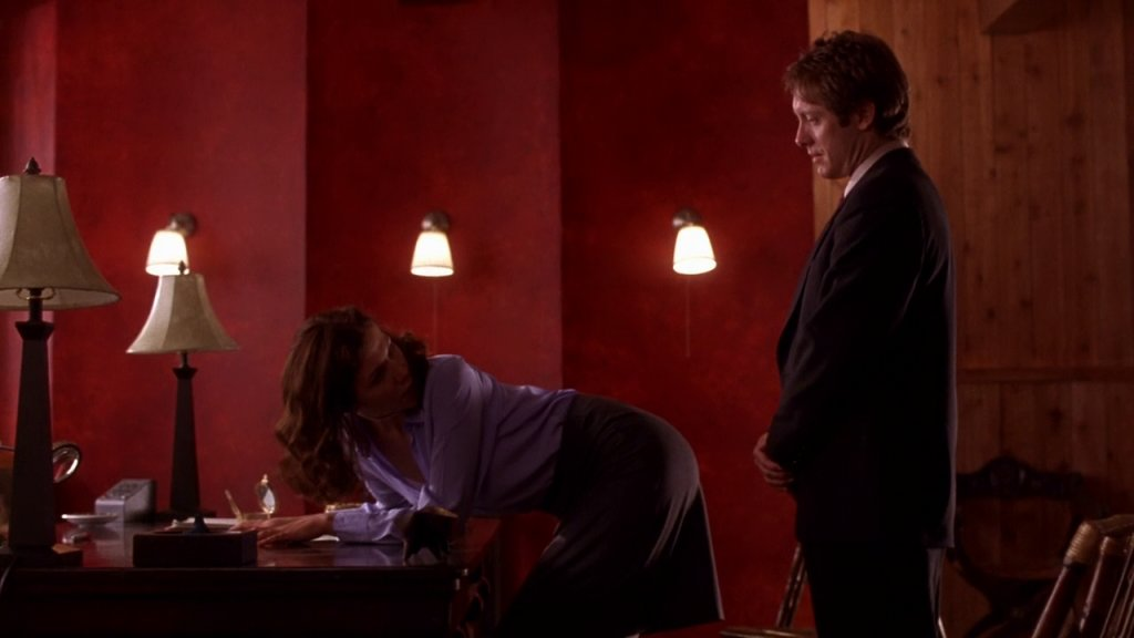 Lee Holloway bends over the desk and looks over her shoulder at Mr Grey