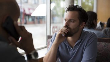 Eddie (Jake Johnson) peers out the window to ponder while inside a diner