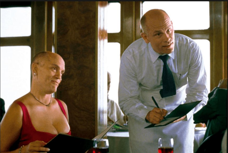 Malkovich inside his own head sees a curvaceous woman and a waiter with his face