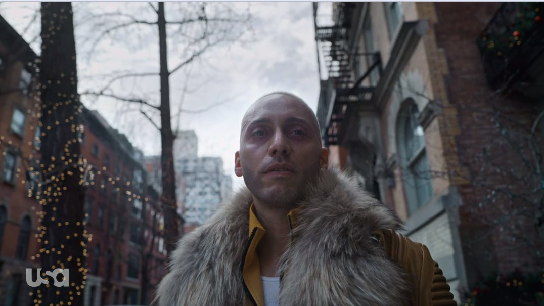 Vera wears a coat with a fur collar