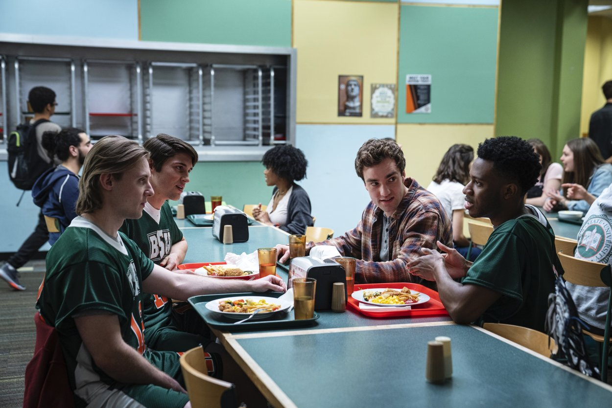 Brendan sits with a group of lacrosse players in uniform in the BSU cafeteria