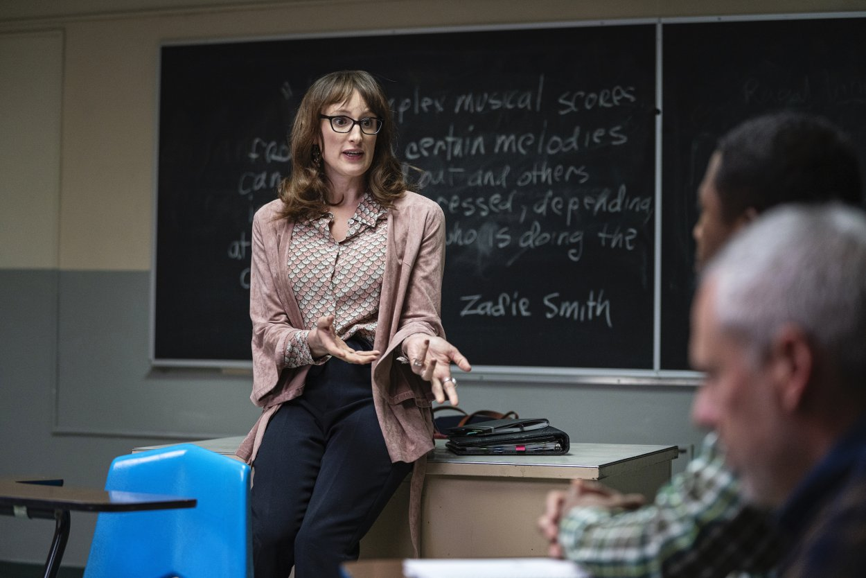 Margo leans against her desk teaching class with a Zadie Smith quote on the blackboard behind her