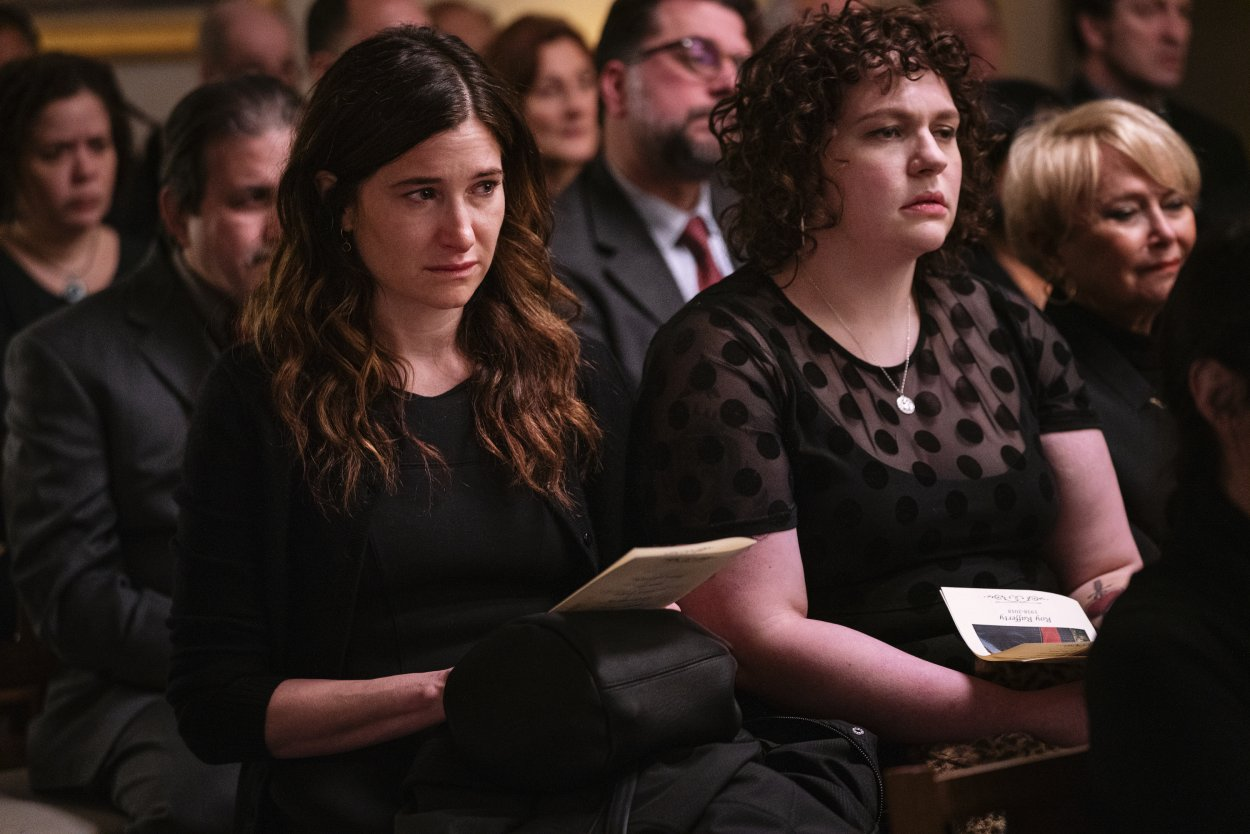Eve and Amanda sit listening to the eulogy at Roy's funeral