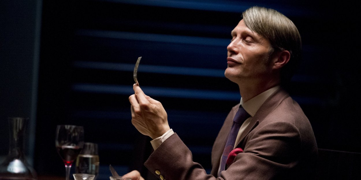 Dr. Lecter at his dinner table, wearing a suit and looking at the fork in his hand with a satisfied smirk on his face