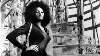 Foxy Brown (Pam Grier) satns on a set of steps near to a wall, with one hand on her hip and a holster visable on the shoulder of her catsuit