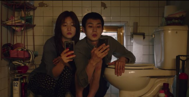 A boy and girl look at their phones as they sit by a toilet
