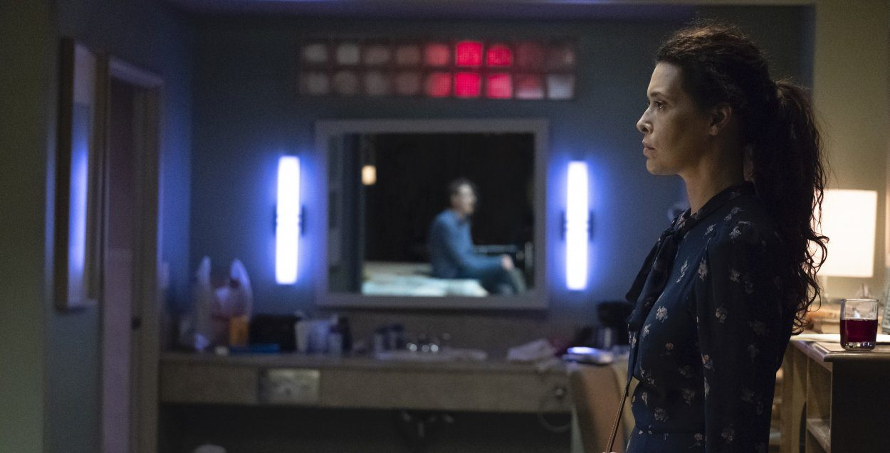Dolores stands in front of the mirror with the reflection of Junior on it, seated on the bed