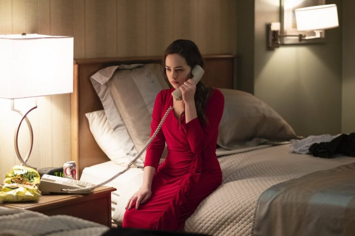 Adrienne sits on the bed in her mothers red dress on the phone