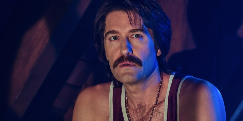Trevor stares into the distance with his hairy chest exposed in a vest in a dark cabin