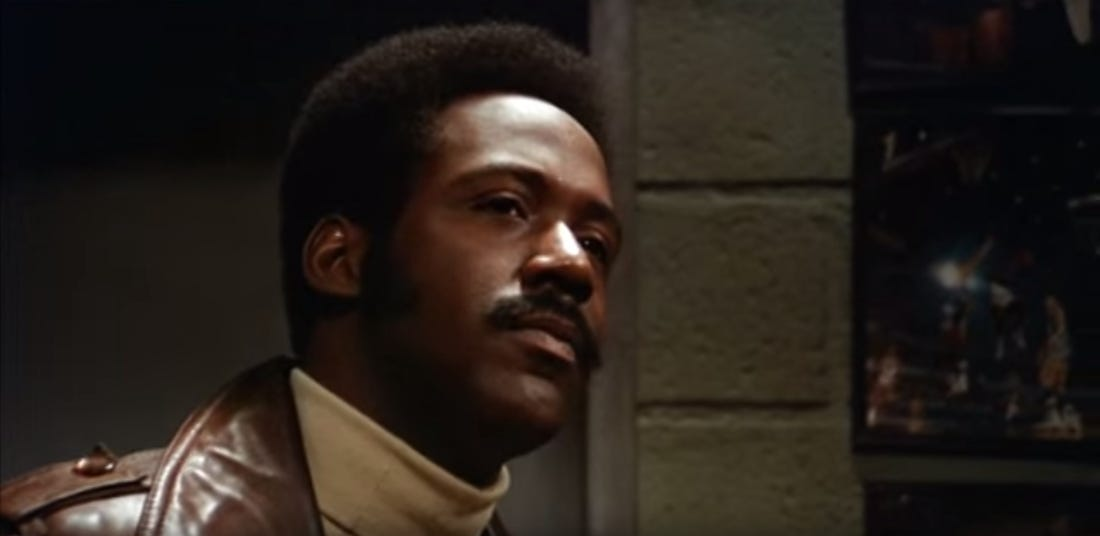 John Shaft (Richard Roundtree) is staring off intot he distance looking thoughtful.