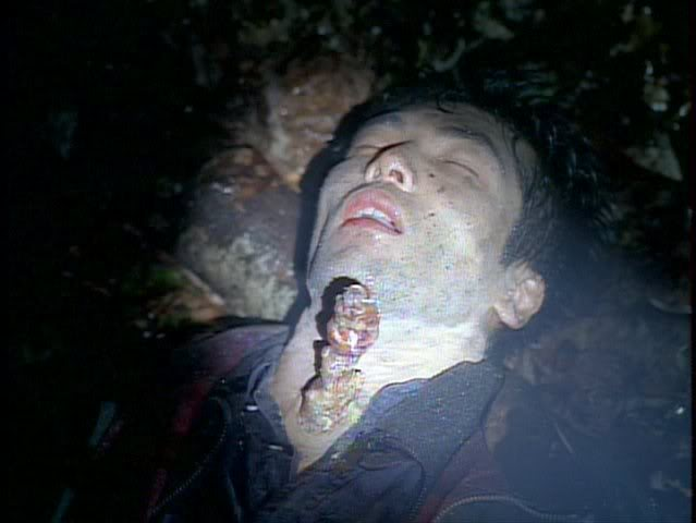 A light shines out into the forest on the body of Tanaka, who's just died when a visible fungus stalk exploded out of his neck.