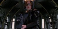 Scully stands in the module that is the entrance to a VR game wearing a VR headset and other game gear and holding a large automatic weapon.