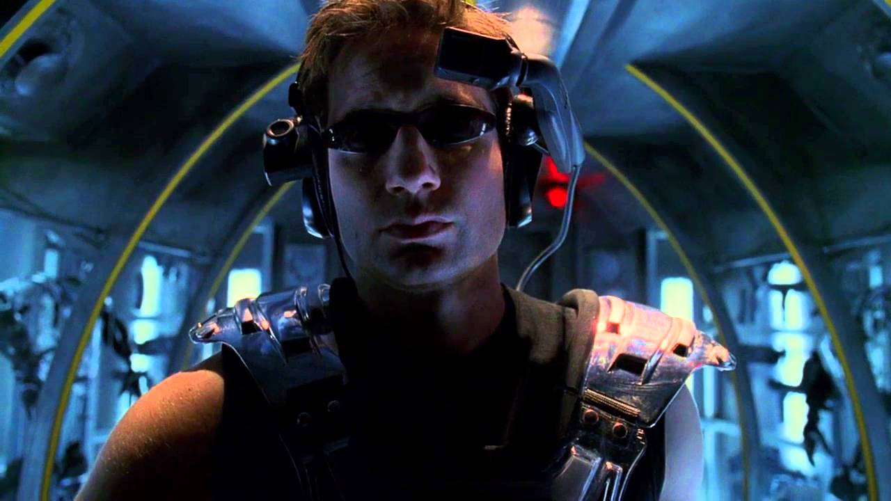 Fox Mulder stands in the module entrance to a VR game wearing dark glasses, a VR headset and other game gear.