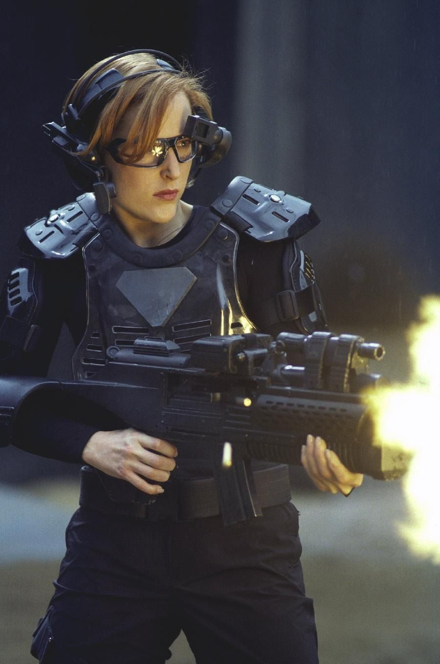 Scully fires a large automatic weapon while wearing a VR headset and other game gear.