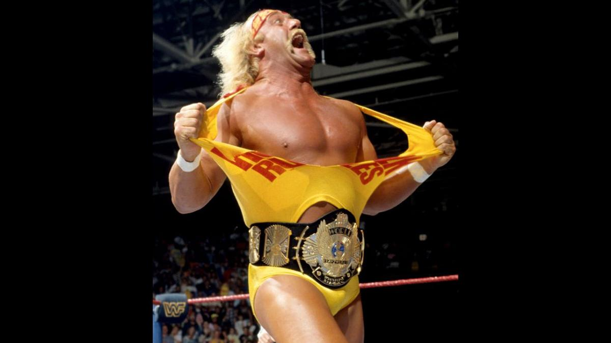 Hulk Hogan stands in a wrestling ring, tearing his T-shirt apart